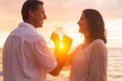 Par som tycker om exponeringsglas av Champene på stranden på solnedgången arkivfoto