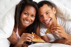 Par som tycker om frukosten i säng Fotografering för Bildbyråer