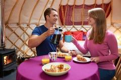 Par som tycker om frukoststunden som campar i traditionella Yurt Arkivbilder