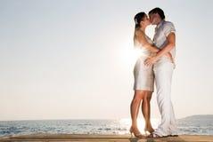 par som tycker om krama sommarsolnedgång Arkivfoto