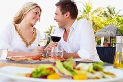 Par som tycker om mål i utomhus- restaurang Royaltyfri Bild