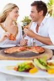 Par som tycker om mål i utomhus- restaurang Arkivbilder