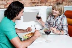 Par som tycker om matställen på en restaurang Arkivfoto