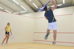 Par som tycker om modig squash i squashdomstol royaltyfria bilder