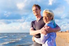 Par som tycker om romantisk solnedgång på stranden Arkivbilder