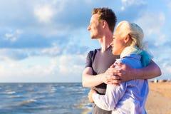 Par som tycker om romantisk solnedgång på stranden Fotografering för Bildbyråer