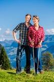 Par som tycker om sikten som fotvandrar i bergen Arkivfoton