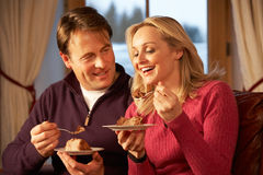 Par som tycker om skivan av caken som sitter på sofaen Royaltyfria Foton