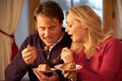 Par som tycker om skivan av caken som sitter på sofaen Royaltyfri Bild