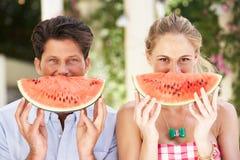 Par som tycker om skivor av vattenmelonen Arkivfoto