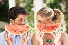 Par som tycker om skivor av vattenmelonen Arkivbild
