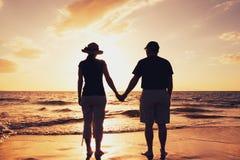 Par som tycker om solnedgång på stranden royaltyfri foto