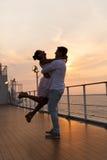 Par som tycker om solnedgångkryssning Arkivbild