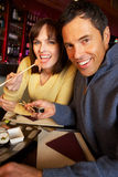 Par som tycker om Sushi i restaurang Arkivfoto