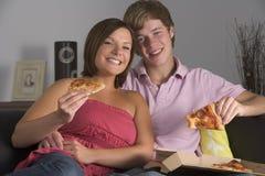 par som tycker om tonårs- pizza royaltyfri foto