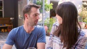 Par som tycker om utomhus- drinkar i trädgård lager videofilmer