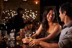 Par som ut tycker om natt på coctailstången royaltyfria foton