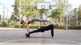 Par som utarbetar på en sportsground som gör enarm plankaövning arkivfoto