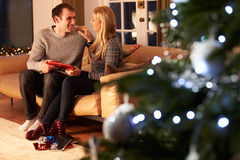 Par som utbyter gåvor vid julgranen Arkivbild