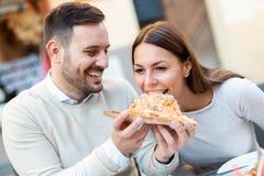 Par som utomhus äter pizzamellanmålet Royaltyfri Bild
