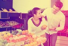 Par som väljer frukter shoppar in Royaltyfria Foton