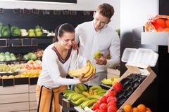 Par som väljer frukter shoppar in Fotografering för Bildbyråer