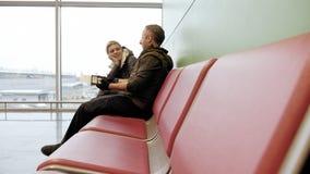 Par som väntar på flygplatsterminalen med biljetter Arkivbild
