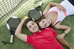 Par som vilar i skoveltennisbana Royaltyfri Foto