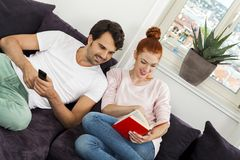 Par som vilar på soffan på vardagsrummet Arkivbild