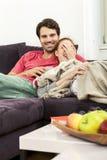 Par som vilar på soffan på vardagsrummet Royaltyfri Foto