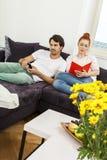 Par som vilar på soffan på vardagsrummet Royaltyfri Fotografi