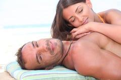 Par som vilar på stranden Arkivbild