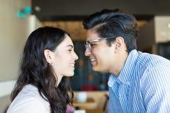 Par som visar positiv känsla av att gilla sig i kafé royaltyfri fotografi