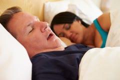 Par sovande i säng med att snarka för man Arkivfoton