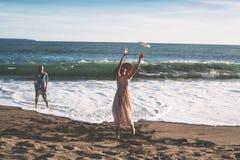 Par spenderar en rolig tid på stranden som spelar med flygplattan Arkivbild