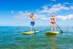Par står upp skoveln som surfar i Hawaii Royaltyfria Bilder