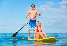 Par står upp skoveln som surfar i Hawaii Arkivbilder