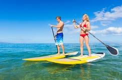 Par står upp skoveln som surfar i Hawaii Royaltyfri Foto