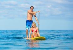 Par står upp skoveln som surfar i Hawaii Arkivfoto