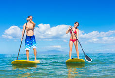 Par står upp skoveln som surfar i Hawaii Arkivfoton
