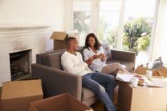 Par tar ett avbrott på den Sofa With Pizza On Moving dagen Royaltyfri Bild