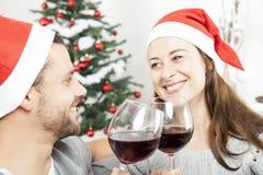 Par tycker om chistmas med vin på soffan Royaltyfria Bilder