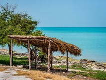Paraíso tropical con un refugio de la palma y de madera en la costa de un océano de la azul-turquesa en México foto de archivo