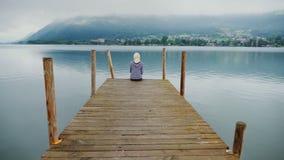 Para admirar a beleza da paisagem em Áustria Uma mulher senta-se em um cais de madeira, olha-se as montanhas e a montanha vídeos de arquivo