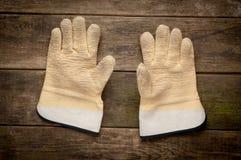 Para arbetshandskar som ligger på plankor av trä Arkivfoto