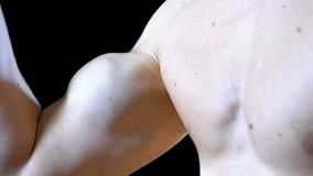 Para arriba bombeado bíceps en una mano del hombre joven en fondo negro almacen de metraje de vídeo
