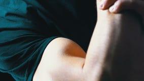 Para arriba bombeado bíceps en una mano del hombre joven en fondo negro y en una camiseta negra metrajes