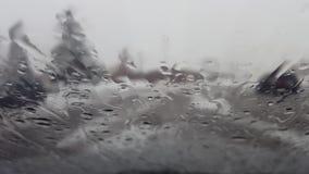 Para arriba-cierre del parabrisas del coche mientras que nieva y llueve el exterior almacen de video