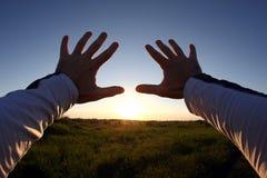 Para arriba levantadas manos en el fondo de la puesta del sol Foto de archivo