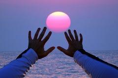 Para arriba levantadas manos en el fondo de la puesta del sol Fotografía de archivo libre de regalías